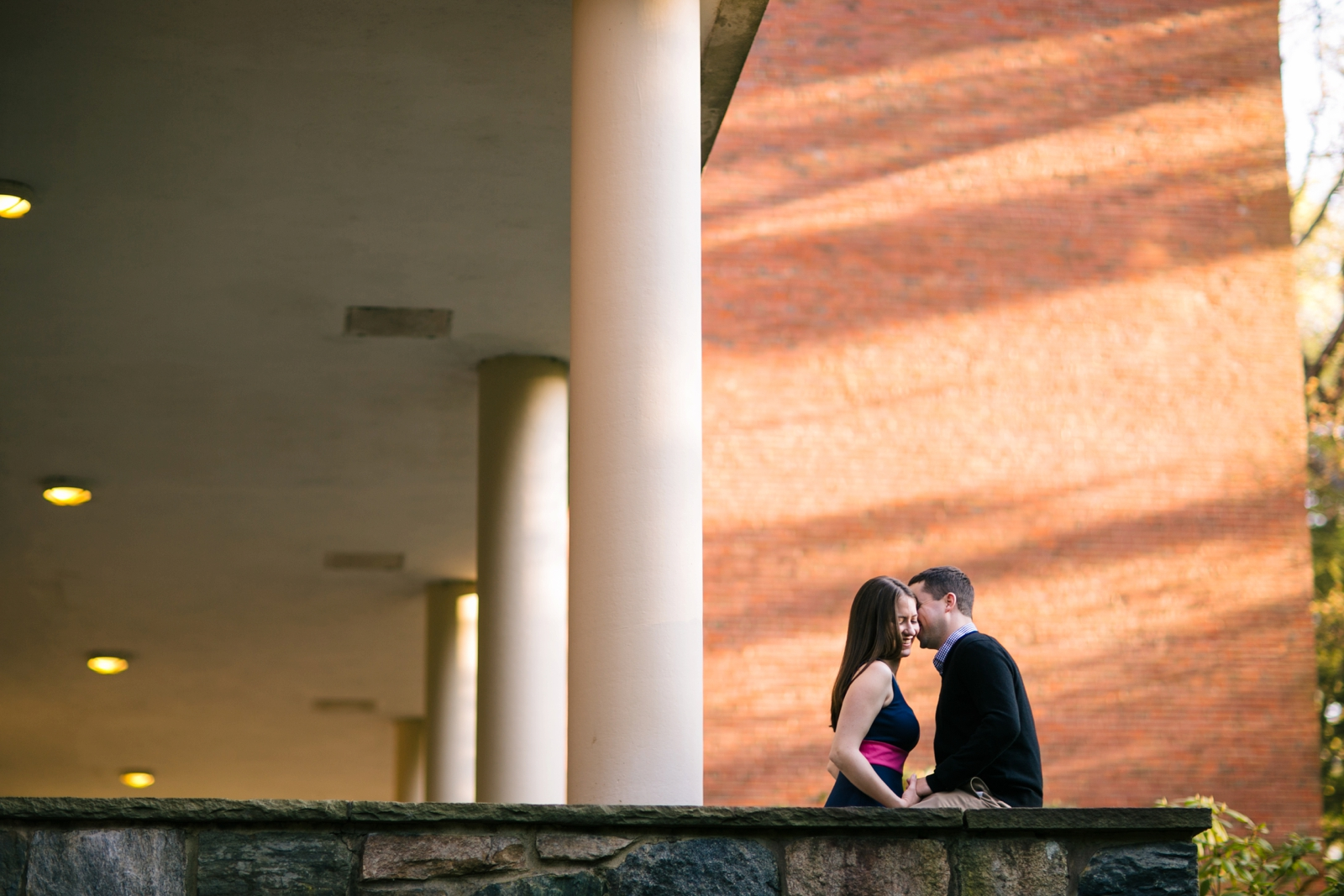 Romantic candid engagement portrait of couple on Wellesley campus.