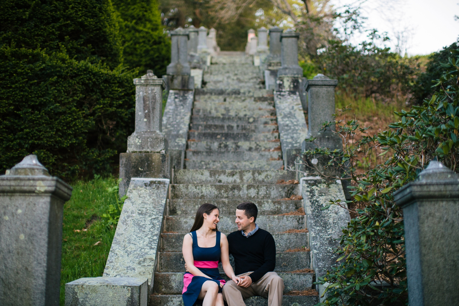 Candid laughing engagement portrait sitting on old stone stairs with soft afternoon light.