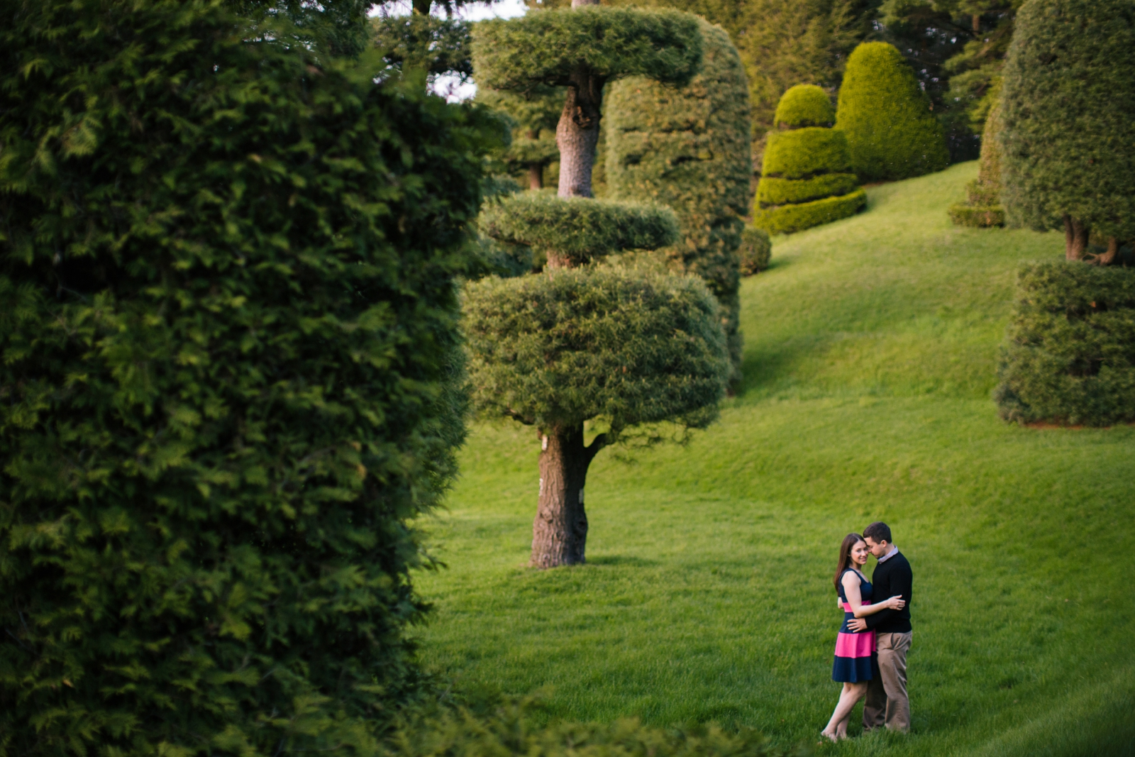 Dreamy engagement portrait in whimsical garden at Wellesley college with golden hour light
