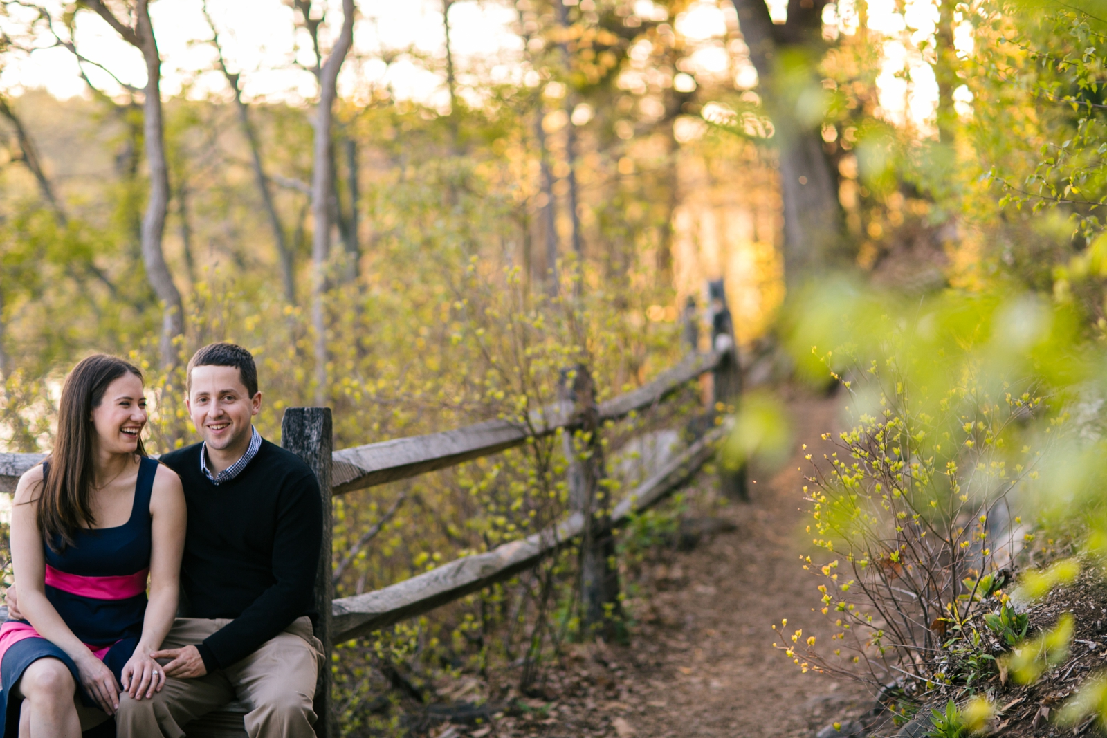 Candid intimate engagement portrait on nature trail with beautiful soft golden hour light