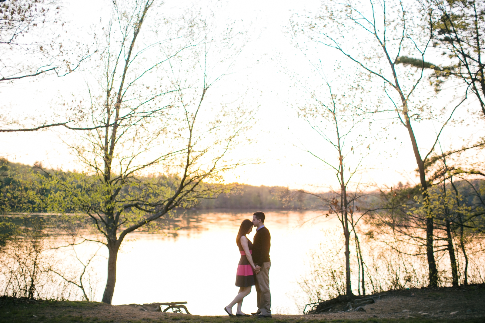 Romantic engagement portrait of silhouette of couple standing in front of lake at sunset